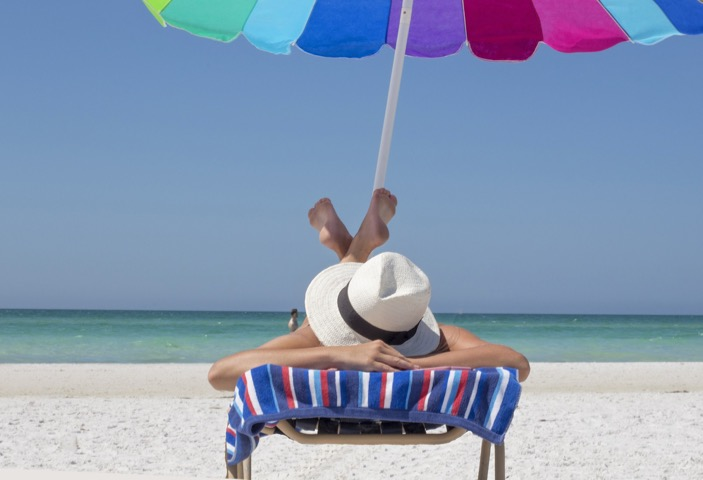 a woman lazing on a sun lounger under a sun umbrella on a beachHow long does it take to be beach body ready / blog / wellbeing / The CountryWives