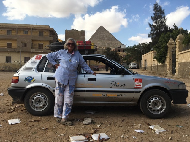 Cape Town Granny leaning against car in front of a Pyramid
