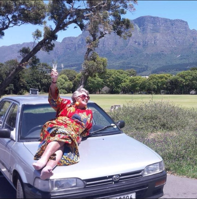 Cape Town Granny on the bonnet of her Toyota car with glass of champagne