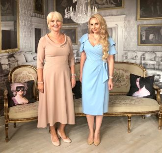 Annabel and Katya each wearing a Bombshell dress in mocha and pale blue