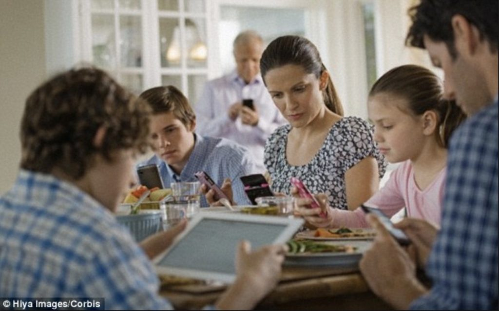 A whole family at a meal on their iPads and iPhones / Manners