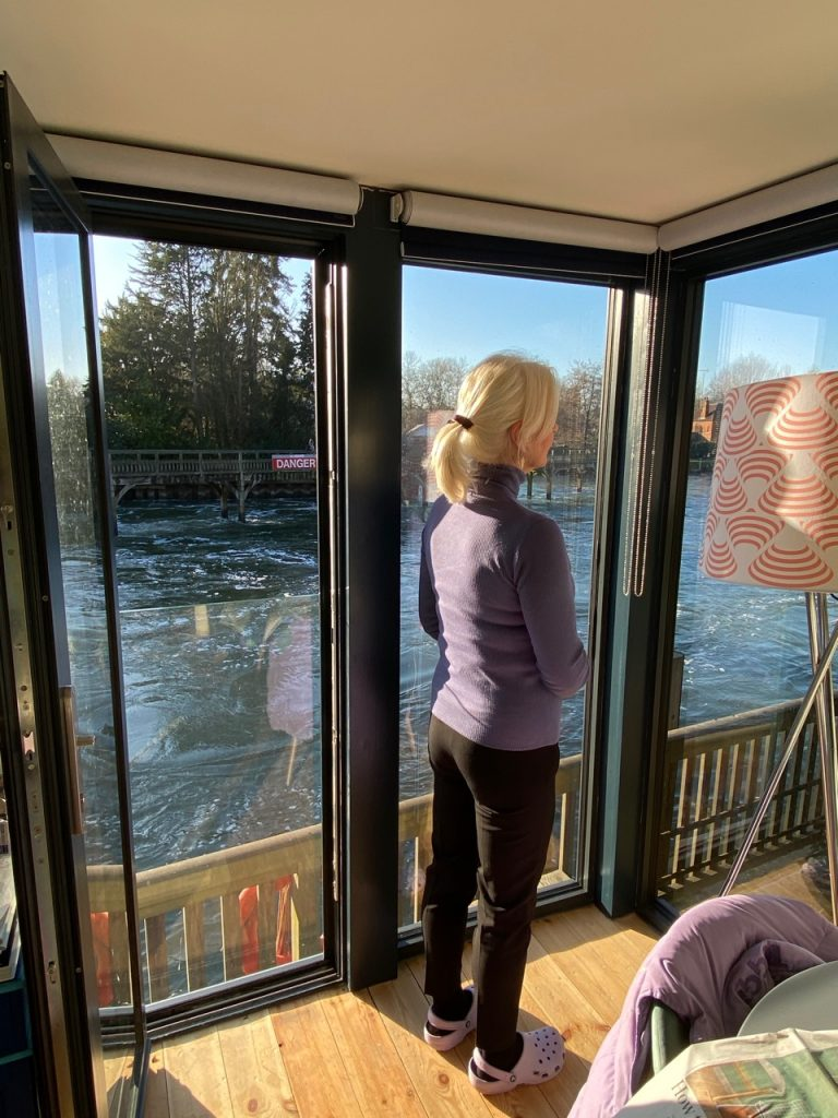 Annabel standing in window of her riverside cabin from post: Could it get any worse?